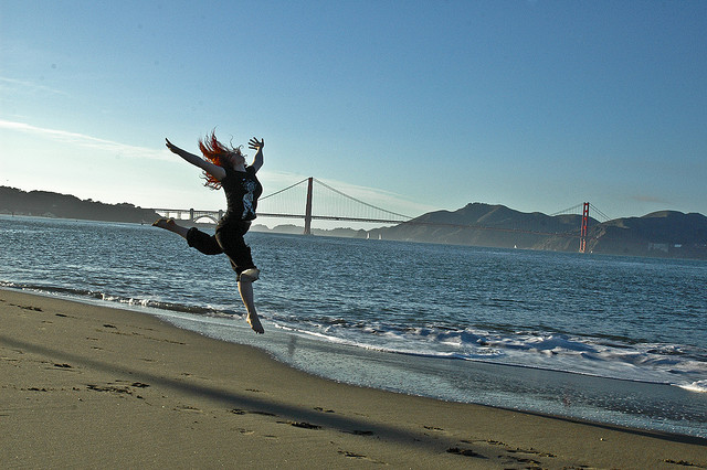 Woman Leaping in the Air at the Beach
