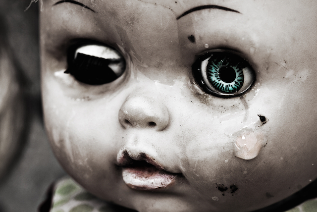 Concept: Abandoned Person. Close up of an old doll`s face with tear. Spesial grunge-fashioned image with grain