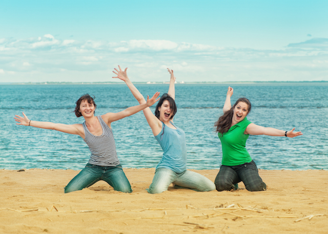Three happy women sitting on the beach