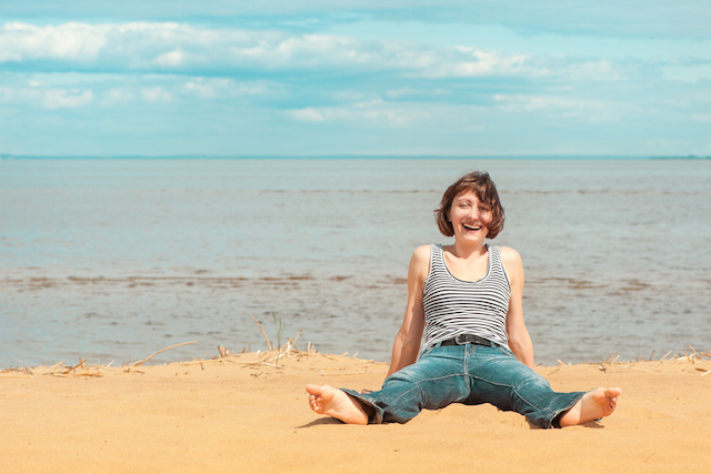 Happy woman sitting on the beach