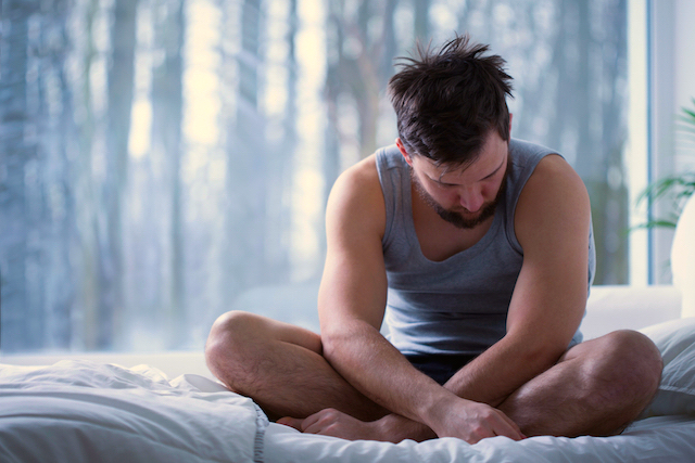 Depressed insomniac man sitting on bed in daylight