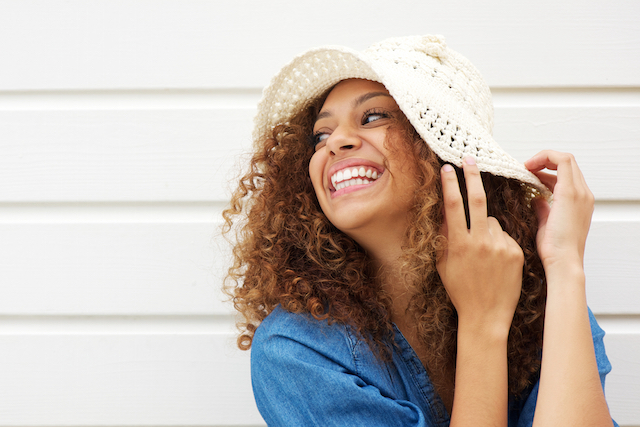 Portrait of a beautiful young woman laughing and wearing summer hat